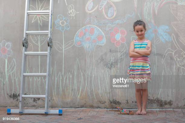 Girl standing next to colourful pictures on a concrete wall