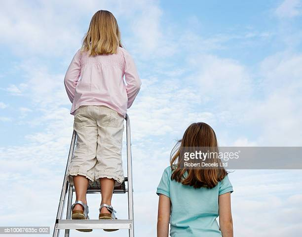 girl (8-9 years) standing next to sister (6-7 years) standing on ladder, rear view - 8 9 years stock pictures, royalty-free photos & images
