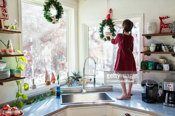 girl standing on a kitchen worktop putting up christmas decorations - 飾りつけ ストックフォトと画像