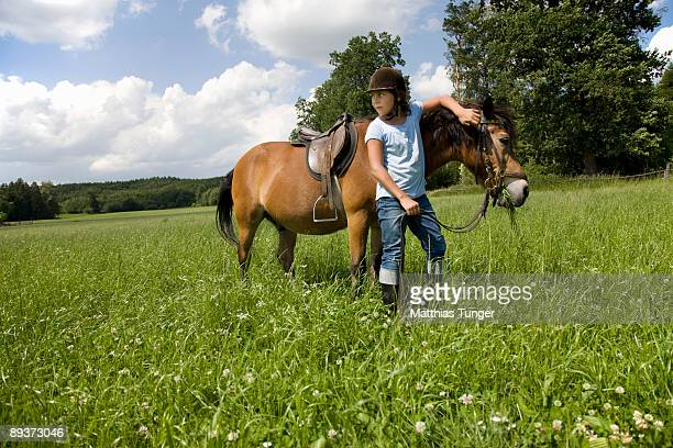 Girl standing on a range with a horse