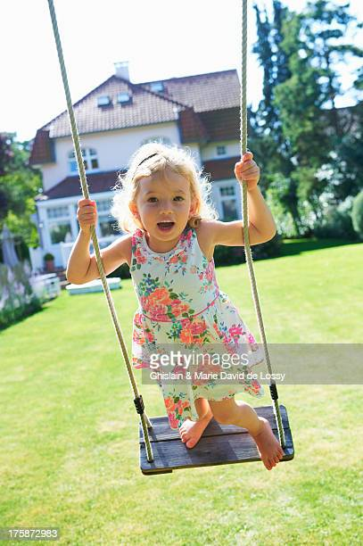 Girl standing on a swing, in the garden