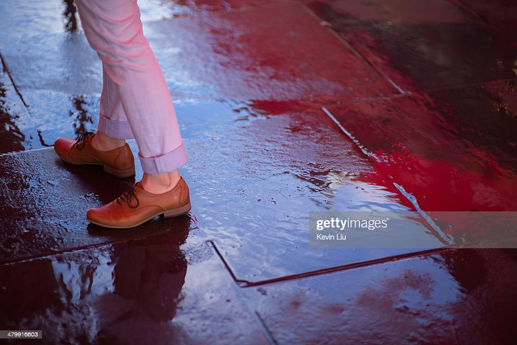 Girl standing on a wet pavement with reflection : Stock Photo