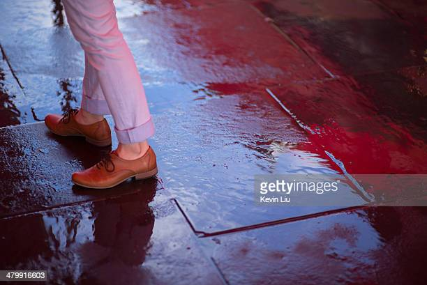 Girl standing on a wet pavement with reflection