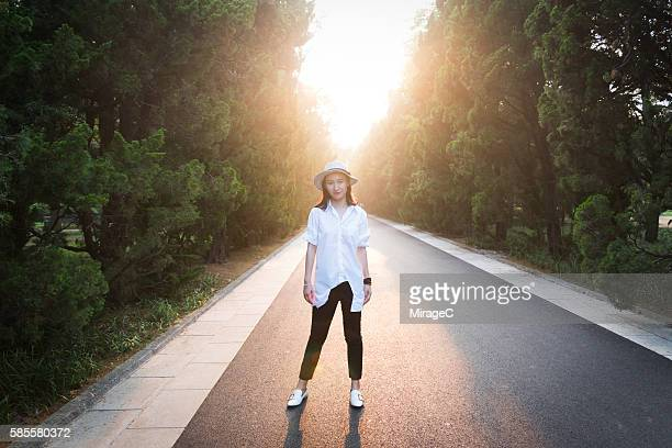 Girl Standing on Avenue with Sunset Glow, Perspective