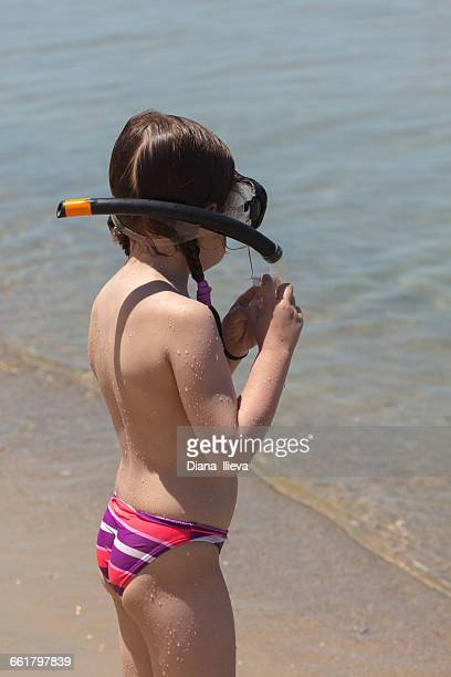Girl standing on beach wearing snorkel and mask