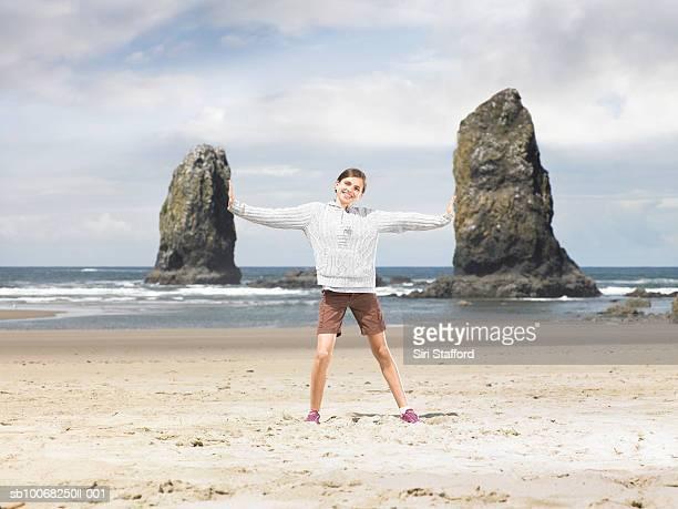 Mädchen (12-13) stehen am Strand mit Ausgestreckte Arme, Lächeln,