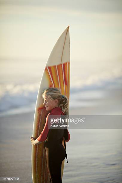 Girl standing on beach with surf board smiling