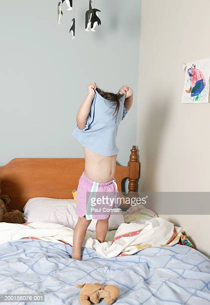 Girl (2-4) standing on bed, pulling shirt over head