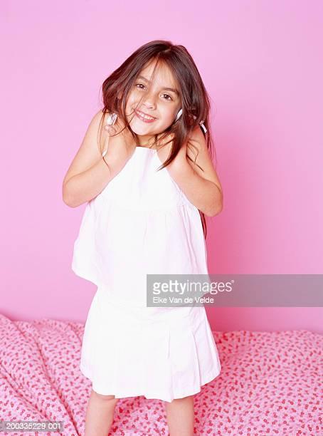 girl (5-7) standing on bed, shrugging, portrait - encogerse de hombros fotografías e imágenes de stock