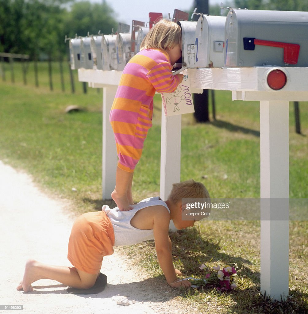 Girl standing on brother's back and peering into mailbox : Stock Photo