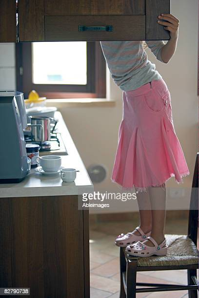 girl standing on chair looking in kitchen cupboard