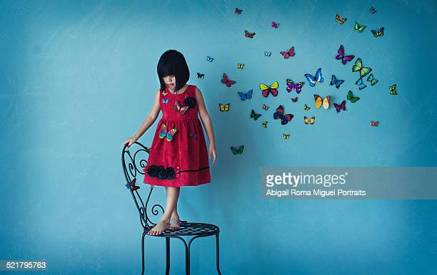 Girl standing on chair with butterflies