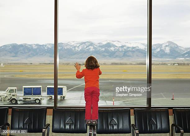 Girl (3-5) standing on chairs, looking out airport window, rear view