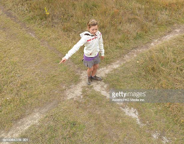 Girl (11-12) standing on crossroad, elevated view