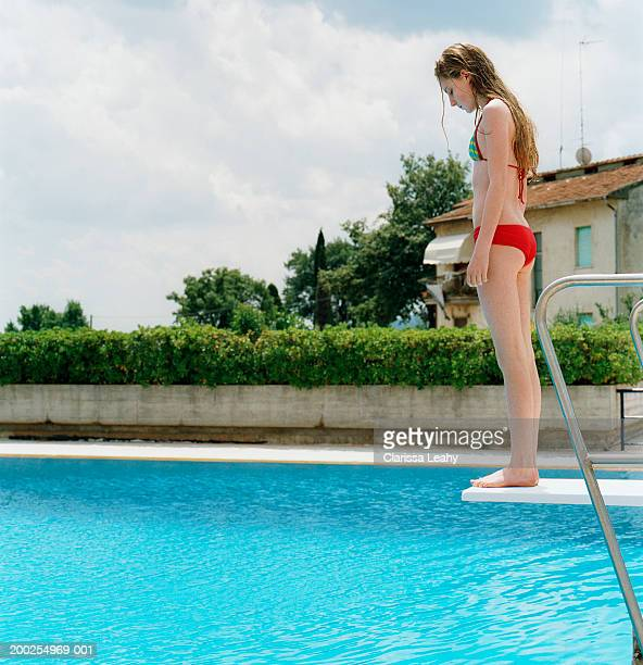 Girl (10-12) standing on edge of diving board over swimming pool