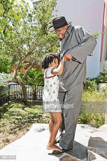 Girl standing on feet of man