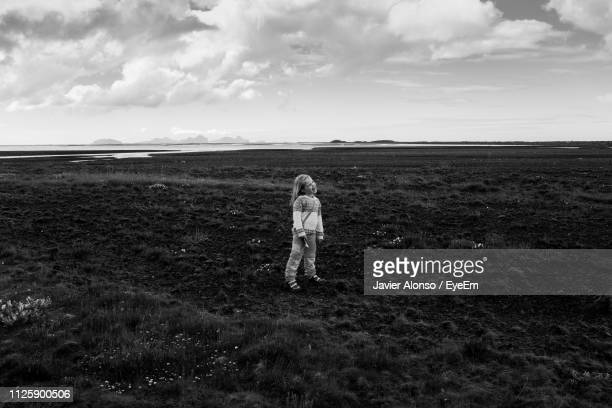 girl standing on field against sky - javier alonso fotografías e imágenes de stock