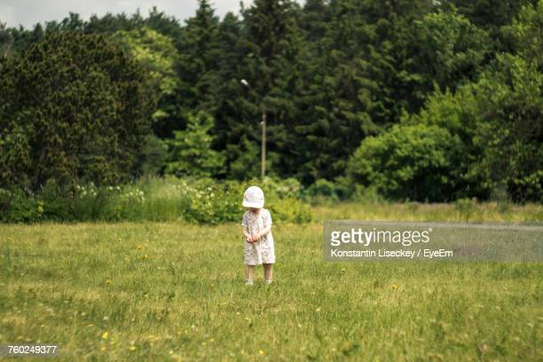 Girl Standing On Grassy Field Against Trees