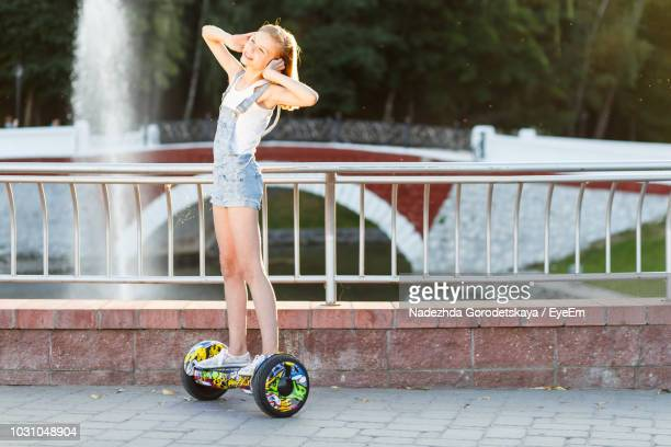 girl standing on hoverboard against bridge - hoverboard stock pictures, royalty-free photos & images