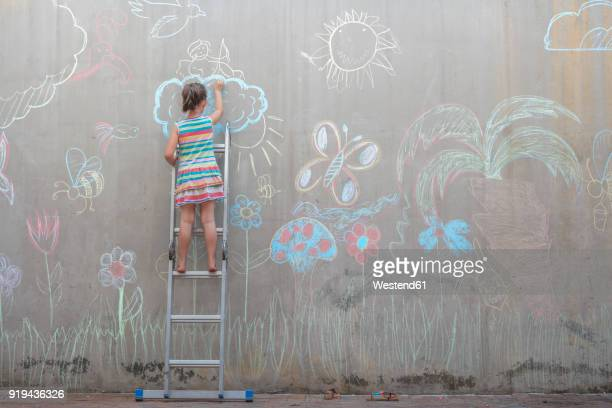 girl standing on ladder drawing colourful pictures with chalk on a concrete wall - vorstellungskraft stock-fotos und bilder