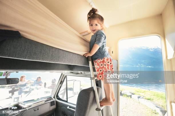 Girl standing on ladder inside of campervan