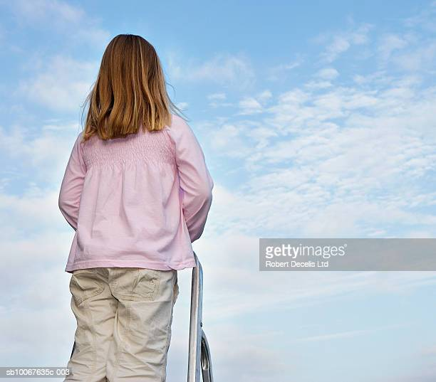 Girl (6-7 years) standing on ladder, looking at clouds, rear view
