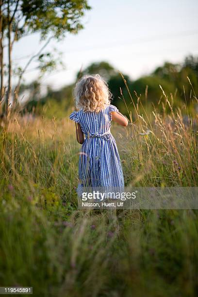 Girl standing on meadow, rear view