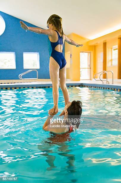 Girl standing on moms hands at a pool