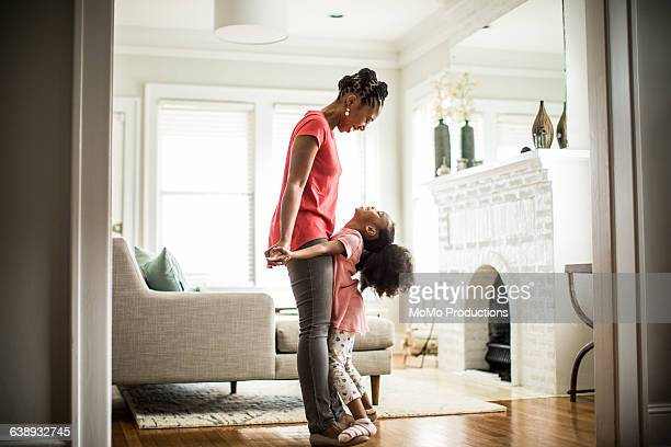 girl standing on mothers feet