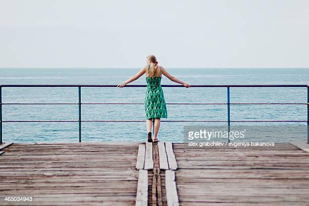 girl standing on old sea pier, russia - grünes kleid stock-fotos und bilder