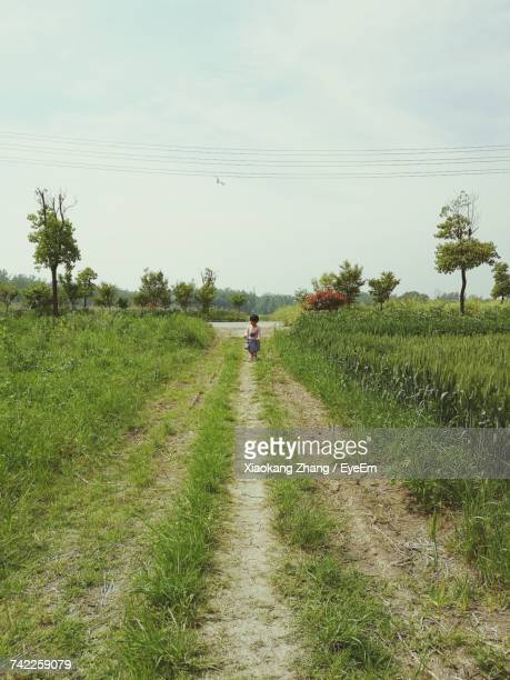 Girl Standing On Pathway Amidst Grassy Field Against Sky