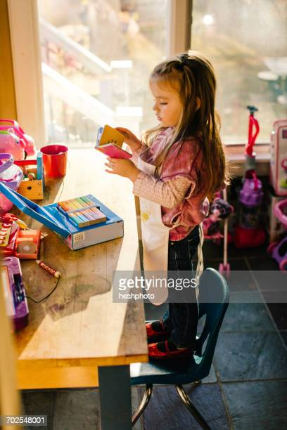 girl standing on playroom chair reading storybook - heshphoto stock pictures, royalty-free photos & images