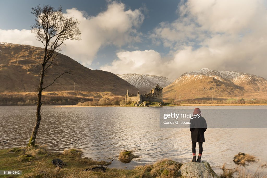 Girl standing on rock beside lake looking at Castle on the distance : Stock Photo