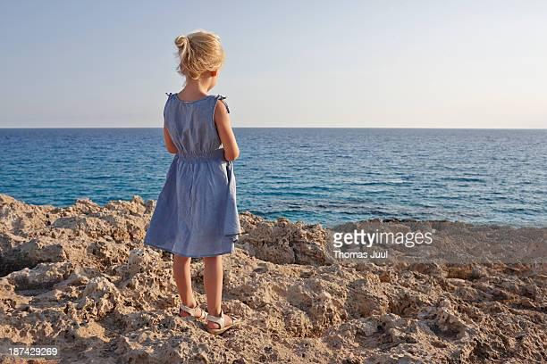 girl standing on rocks and looking over the sea - vista posteriore foto e immagini stock