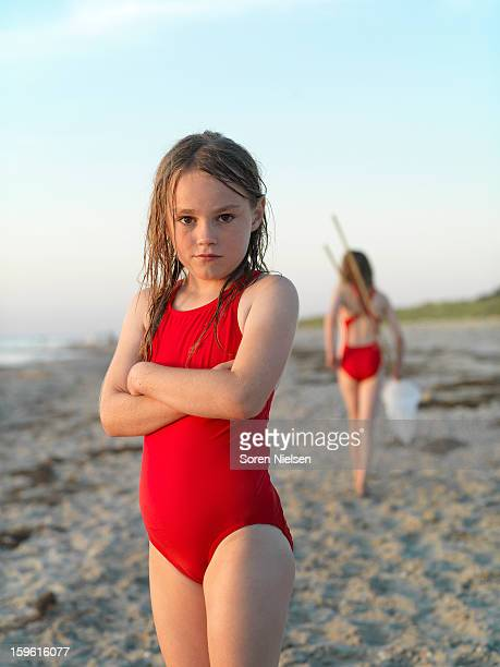 girl standing on sandy beach - swimwear stock photos and pictures