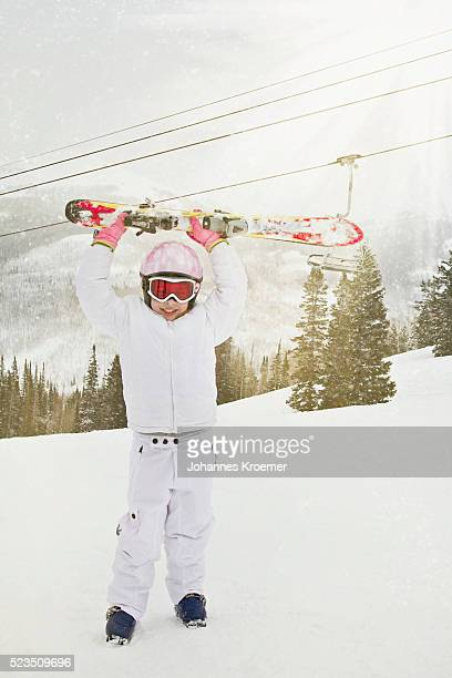 girl (7-9) standing on ski slope and holding skies above head - ski wear stock pictures, royalty-free photos & images
