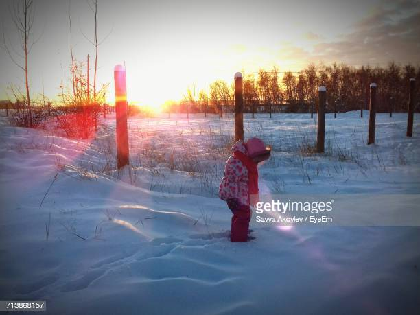 Girl Standing On Snow Covered Field Against Sky During Sunset