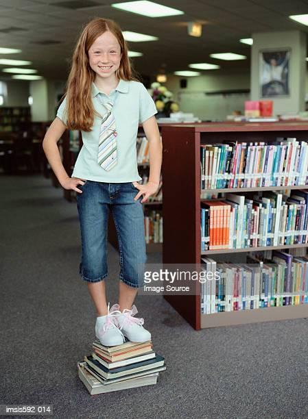 Mädchen auf Stapel Bücher