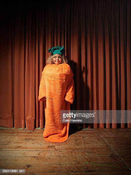 Girl (5-7) standing on stage wearing carrot costume, looking away