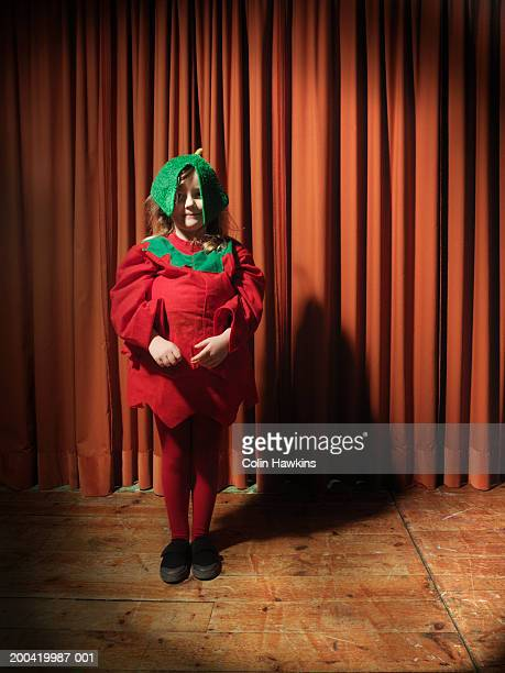Girl (4-6) standing on stage wearing tomato costume, portrait