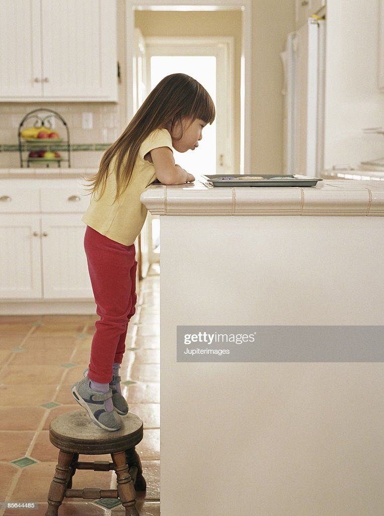 Girl standing on stepstool looking at cookies : Stock Photo