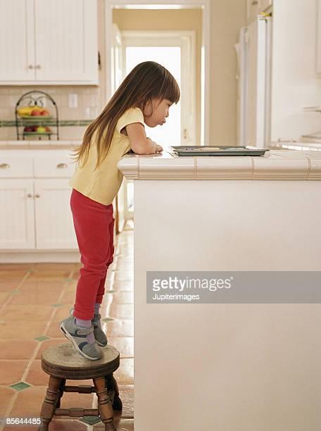 Girl standing on stepstool looking at cookies