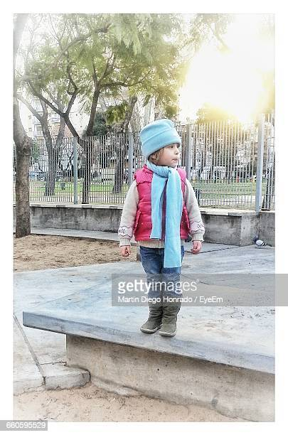 Girl Standing On Stone Bench At Park