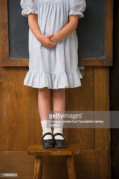"girl (6-7) standing on stool in front of blackboard, low section - ""compassionate eye"" fotografías e imágenes de stock"