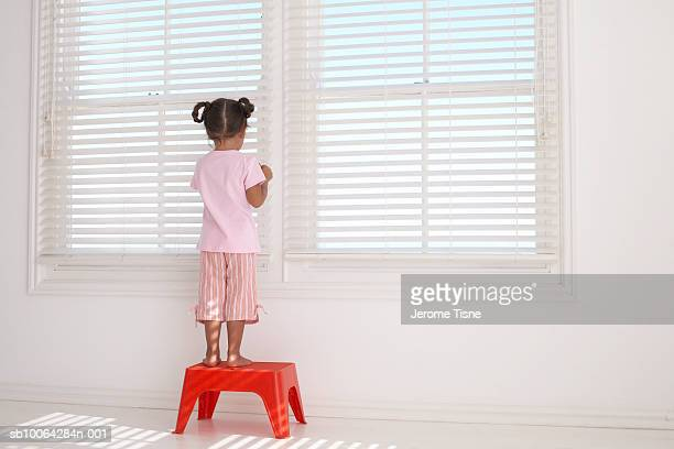 Girl (2-3) standing on stool looking through window, rear view