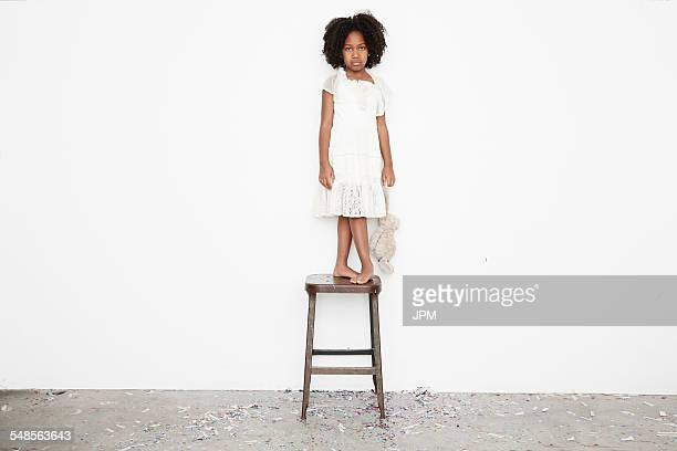 Girl standing on stool sulking and holding teddy bear