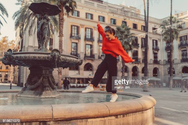 girl standing on tip toes at the fountain - barcelona spain stock pictures, royalty-free photos & images