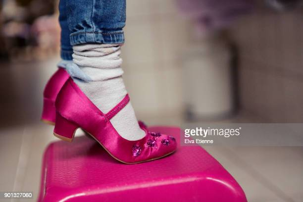 girl (4-5) standing on tiptoes in high heels and oversized socks, on a step - pink sock image stock pictures, royalty-free photos & images