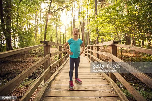Girl standing on wooden bridge in the woods