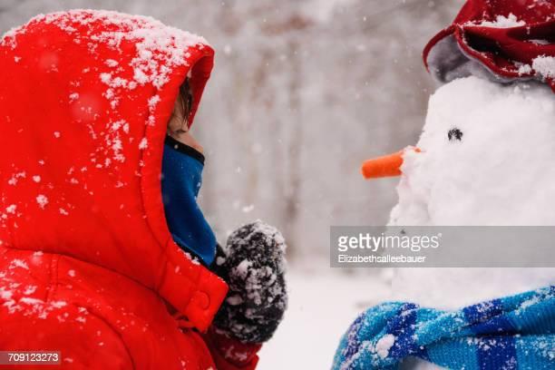 Girl standing opposite a snowman